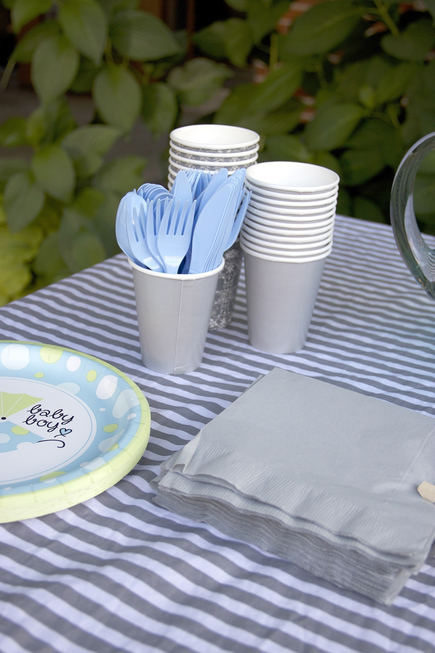 gray cups blue cutlery and colored napkins for a lamb themed baby shower