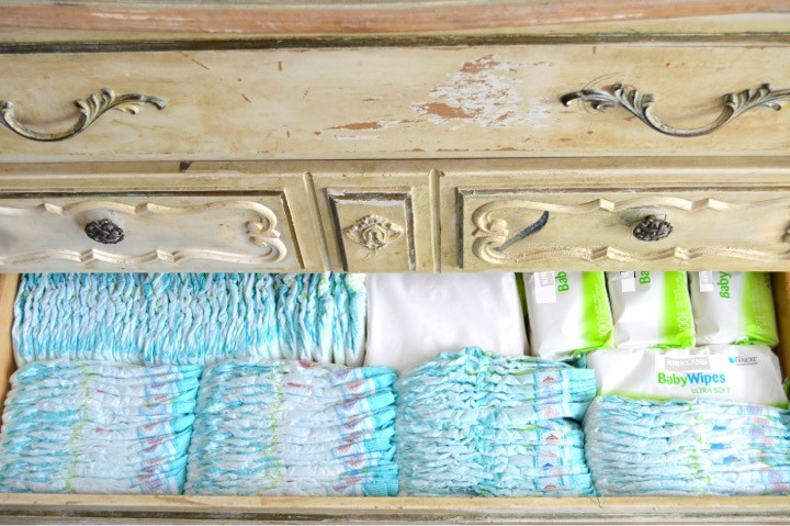 Buy diapers and wipes in bulk | Tips for how to make a practical diaper changing station. Changing table ideas like: repurpose a dresser, get a Diaper Genie, buy diapers and wipes in bulk, baby changing pad + more ideas for your baby's nursery. DIY dresser changing table hack. Tips and tricks for when baby comes like where to go shopping for a diaper pail.
