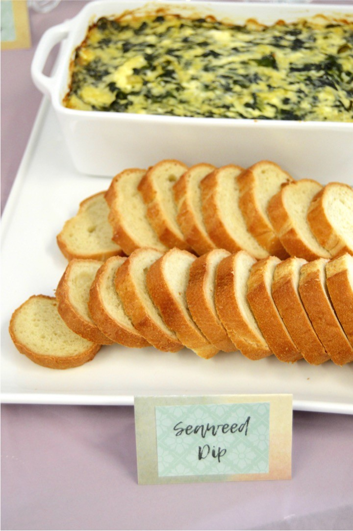 Seaweed Dip is spinach artichoke dip with bread. Themed nautical food. Sailing baby shower inspiration with a nautical theme. Food, party decorations, invitation, games, + gift ideas for an adventure sailing girl's baby shower.