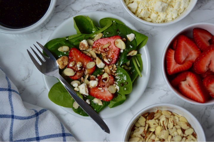 Strawberry Spinach Salad with sliced almonds, feta cheese, and a Honey Balsamic Vinaigrette Dressing | Easy Easter dinner menu for the family. Fresh, springtime dinner with vegetable lasagna main course, strawberry spinach salad, rolls, + milkshake dessert.