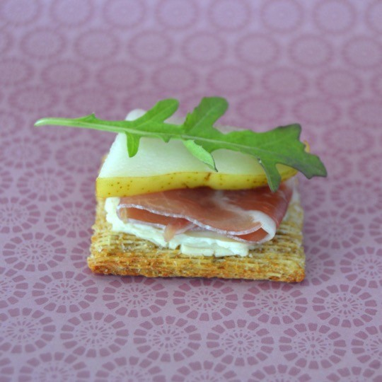 Step 4 - Top with arugula. Fancy cheese and crackers recipe for the foodie with TRISCUIT Crackers, creamy cheese spread, prosciutto, pear, and arugula leaves. Perfect appetizer or snack. Delicious food to make for a party or just for fun with the kids.