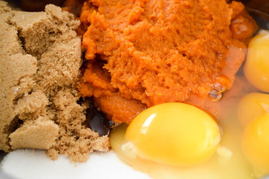 Pumpkin, eggs, sugar, brown sugar, and other ingredients for making moist pumpkin muffins