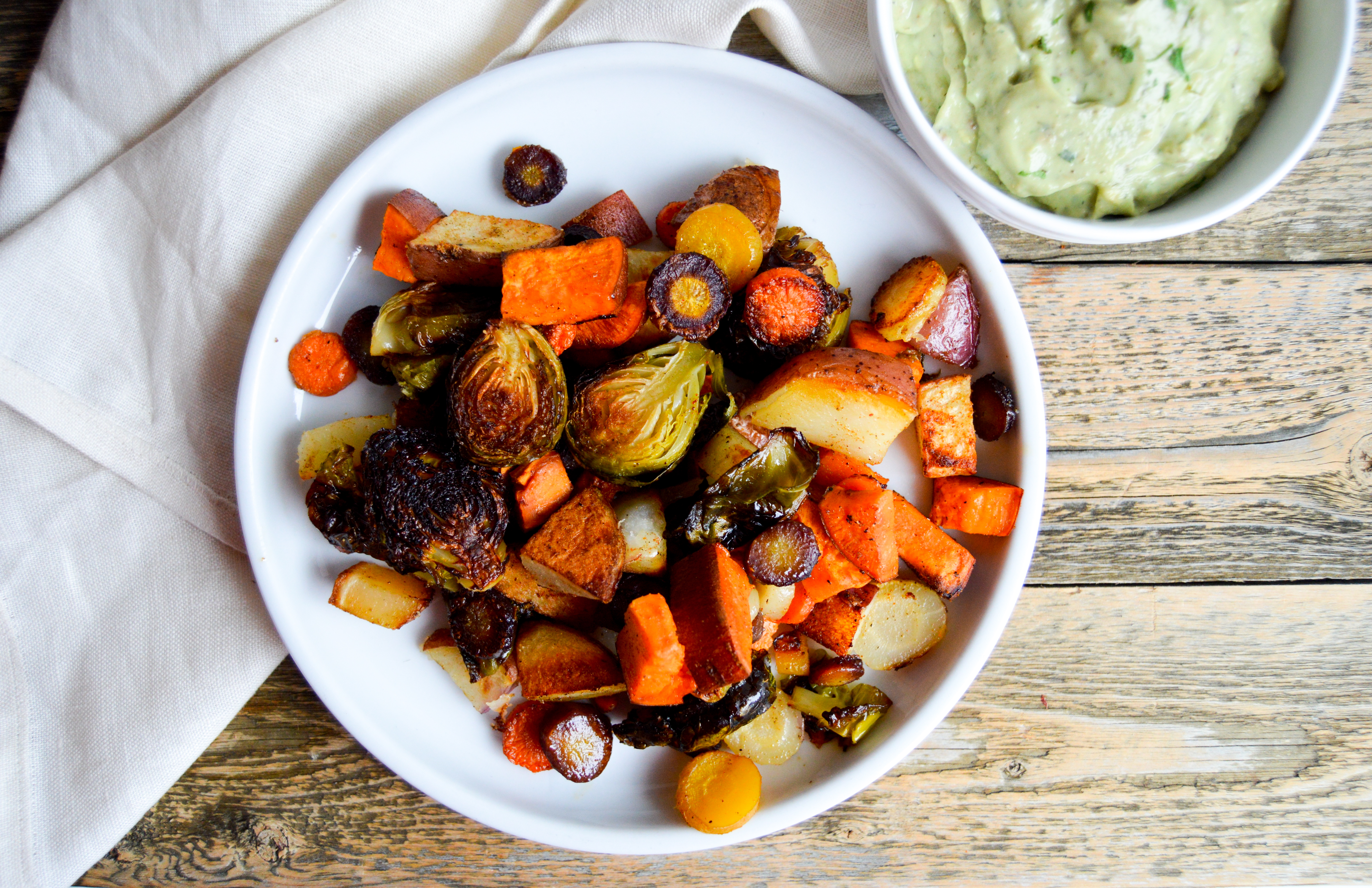 Recipe for baking hearty sheet pan veggies and avocado ranch dip recipe. Vegetable filled dinner idea for a healthy meal. Corn oil and avocado substitutions. Rainbow carrots, brussels sprouts, sweet potato, and red potato veggies baked with corn oil and seasonings. Delicious, easy, healthy dinner dish.